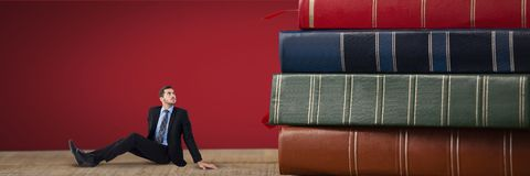 Business man looking up and sitting next to a pile of books. Digital composite of Business man looking up and sitting next to a pile of books Royalty Free Stock Images