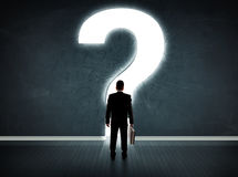 Business man looking at wall with a bright question mark Royalty Free Stock Photo