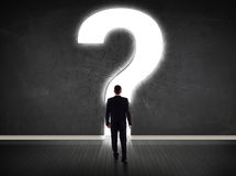Business man looking at wall with a bright question mark Royalty Free Stock Images