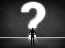 Business man looking at wall with a bright question mark Stock Images