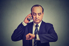 Business man looking at wrist watch, talking on mobile phone running late for meeting. Time is money Stock Photos