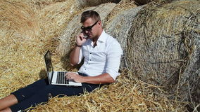 Business man looks beautiful works with a laptop and talking on the phone sitting in a haystack. Summer holidays in the stock footage