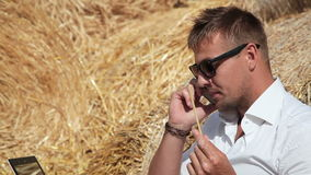 Business man looks beautiful works with a laptop and talking on the phone sitting in a haystack. Summer holidays in the stock video