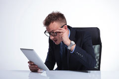 Business man looks at his tablet with awe Stock Photos