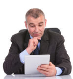 Business man looks pensively at his tablet Royalty Free Stock Photo