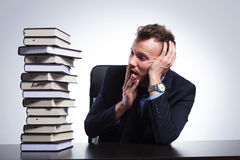 Business man looks at pile of books Royalty Free Stock Photos