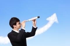 Business man looks through a telescope stock photo