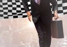 Business man lower body against skyline with flare and checkered flag. Digital composite of Business man lower body against skyline with flare and checkered flag Royalty Free Stock Photos