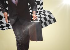 Business man lower body with briefcase against yellow background and checkered flag Stock Photo