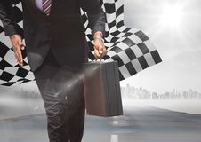 Business man lower body with briefcase on road with skyline and checkered flag. Digital composite of Business man lower body with briefcase on road with skyline Royalty Free Stock Photography
