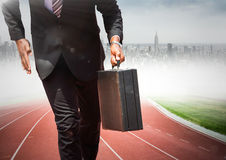 Business man lower body with briefcase on track against blurry skyline Stock Image