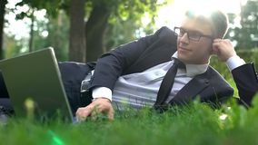 Business man lying on grass in park and working on laptop, harmony with nature. Stock photo stock image