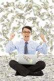 Business man make a victory gesture with money rain Stock Image