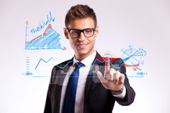 Business man making a good choice. Young business man making a choice by tapping on a virtual screen and changing the order of things for the better Stock Images