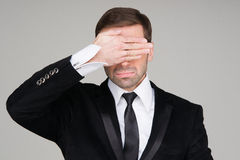 Business man making the see no evil gesture. Businessman covering his eyes with his hand royalty free stock images