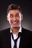 Business man  making a silly face. Young businessman with tie undone, making a silly face.Crosseyed young businessman with mouth up to his ears. On black Royalty Free Stock Photo