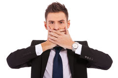 Business man making the speak no evil gesture. Over white . young businessman covering his mouth with his hand royalty free stock photography