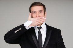 Business man making the speak no evil gesture. Businessman covering his mouth with his hand stock photography