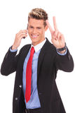 Business man making victory on phone Royalty Free Stock Photo