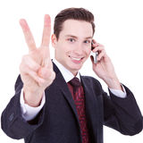 Business man making victory sign on phone Royalty Free Stock Photo