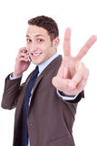 Business man making victory sign on phone Royalty Free Stock Images