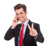 Business man making victory sign on phone stock images