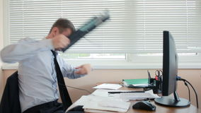 Business man, manager in anger smashes keyboard on desk, sitting in office