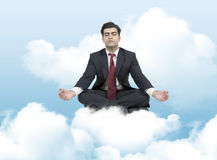 Business man meditates on clouds Stock Images