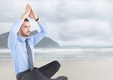 Business man meditating against blurry beach. Digital composite of Business man meditating against blurry beach Stock Images