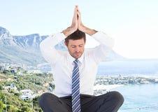 Business man meditating against blurry coastline stock images