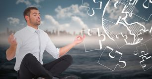 Business man meditating against blurry skyline and water with white jigsaw doodle. Digital composite of Business man meditating against blurry skyline and water Royalty Free Stock Image