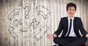 Business man meditating against blurry wood panel with math doodle Royalty Free Stock Photo