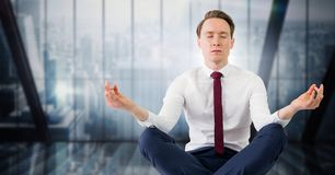 Business man meditating against dark blue blurry window Stock Image