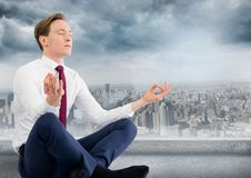 Business man with meditating against grey skyline and clouds. Digital composite of Business man with meditating against grey skyline and clouds Stock Photography