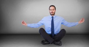Business man meditating against grey wall. Digital composite of Business man meditating against grey wall Stock Images