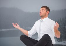Business man meditating against misty river and trees with grey sky Stock Photography