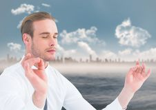 Business man meditating against water and skyline. Digital composite of Business man meditating against water and skyline Royalty Free Stock Photo