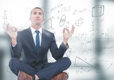 Business man meditating in blurry grey office with flare and math doodle. Digital composite of Business man meditating in blurry grey office with flare and math stock photography