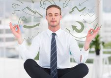 Business man meditating in blurry white office surrounded by green arrow doodles Stock Photos