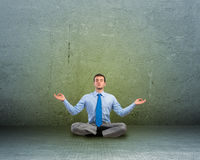 Business man meditating on floor Stock Photo