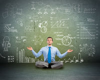 Business man meditating on floor. Image of a business man meditating on floor, wall charts and diagrams are drawn Stock Images