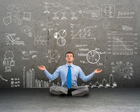 Business man meditating on floor. Image of a business man meditating on floor, wall charts and diagrams are drawn Royalty Free Stock Image