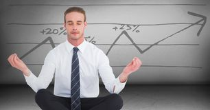 Business man meditating in grey room against graph. Digital composite of Business man meditating in grey room against graph Stock Photos