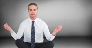 Business man meditating in grey room Royalty Free Stock Images
