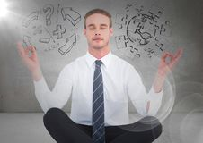 Business man meditating in grey room with flare and jigsaw, arrow doodles. Digital composite of Business man meditating in grey room with flare and jigsaw, arrow Royalty Free Stock Photos