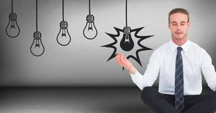 Business man meditating in grey room with lightbulb graphics. Digital composite of Business man meditating in grey room with lightbulb graphics Royalty Free Stock Photo