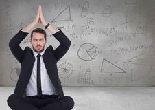 Business man meditating in grey room with math doodles. Digital composite of Business man meditating in grey room with math doodles Stock Photos