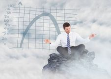 Business man meditating on mountain peak among clouds against blue graph. Digital composite of Business man meditating on mountain peak among clouds against blue Stock Photo