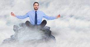Business man meditating on mountain peak in the clouds. Digital composite of Business man meditating on mountain peak in the clouds Royalty Free Stock Photography
