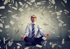 Mature business man meditating under money rain Stock Photo